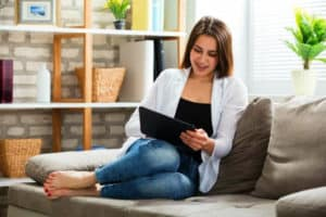 woman-sitting-using-tablet-on-sofa-How To Get Rid Of Cat Allergies-
